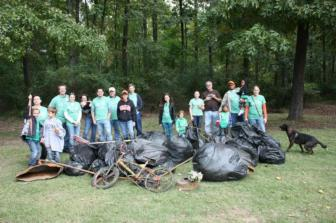 Group of Watershed Stewards with a mound of trash collected from a local stream